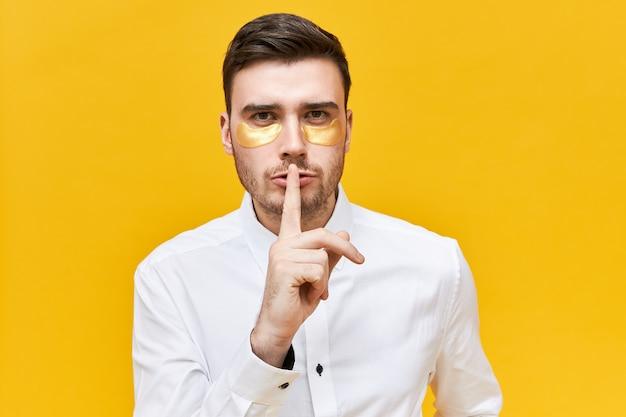 Ernstige jonge man in wit overhemd houdt de vinger op zijn lippen, maakt een zwijg gebaar, vraagt om te zwijgen en zijn geheim niet te vertellen, draagt onder ooglapjes terwijl hij slaapgebrek of een kater heeft Gratis Foto