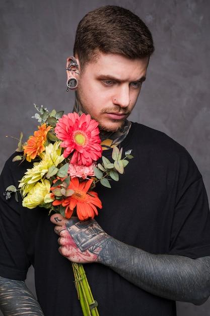 Ernstige jonge man met een gepiercete neus en oren bloemboeket in de hand te houden Gratis Foto