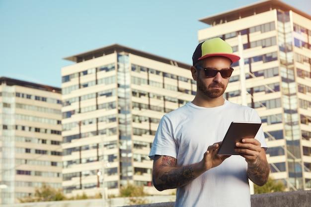 Ernstige jonge man met een wit effen t-shirt en een rode, gele en zwarte vrachtwagenchauffeurhoed die naar zijn tablet kijkt tegen stadsgebouwen en lucht Gratis Foto