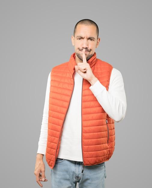 Ernstige jonge man vraagt om stilte gebaren met zijn vinger Premium Foto