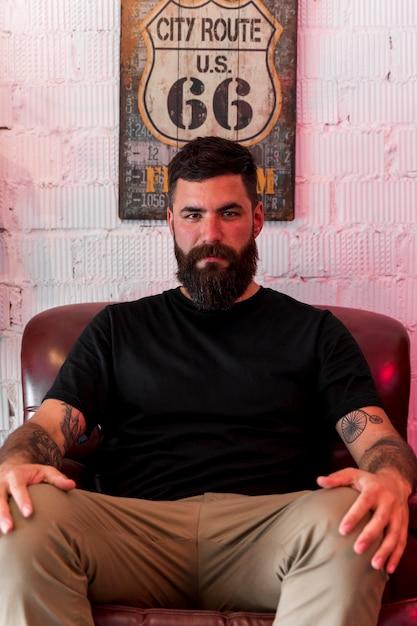 Ernstige jonge man zittend op fauteuil in salon Gratis Foto