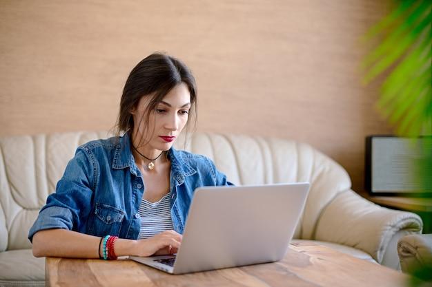 Ernstige jonge vrouw die aan laptop in bureau werkt Gratis Foto