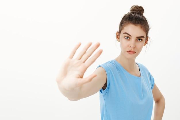 Ernstige jonge vrouw die zegt te stoppen, nee te zeggen, één hand uit te steken in een gebaar van verbod, waarschuwing of afkeuring Gratis Foto