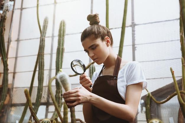 Ernstige jonge vrouw die zich in serre dichtbij installaties bevindt Gratis Foto