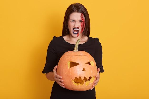 Ernstige jonge vrouw, gekleed in zwarte jurk, op zoek schreeuwend, dame spreekt woede, meisje in halloween kostuum geïsoleerd op geel met pompoen in handen. Gratis Foto