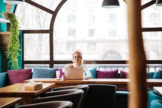 Ernstige jonge vrouw zitten en met behulp van laptop in café Gratis Foto