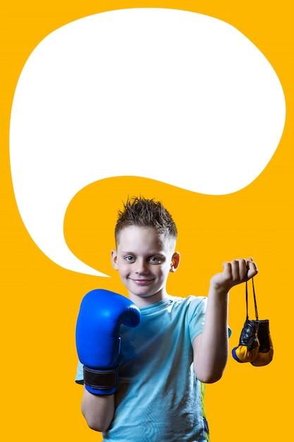 Ernstige jongen in blauwe bokshandschoenen op heldere gele achtergrond Premium Foto