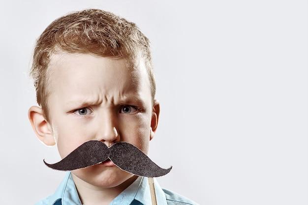 Ernstige jongen met een grote snor fronste tegen het grijs Premium Foto