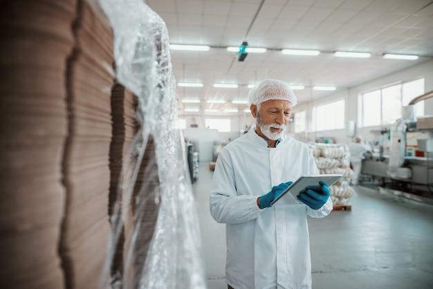 Ernstige kaukasische senior volwassen inspecteur gekleed in wit uniform met behulp van tablet voor kwaliteitsbeoordeling van voedsel in voedselplant. Premium Foto