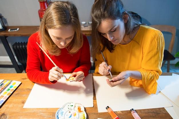Ernstige kunstenaar twee die met penseel en palet werkt Gratis Foto
