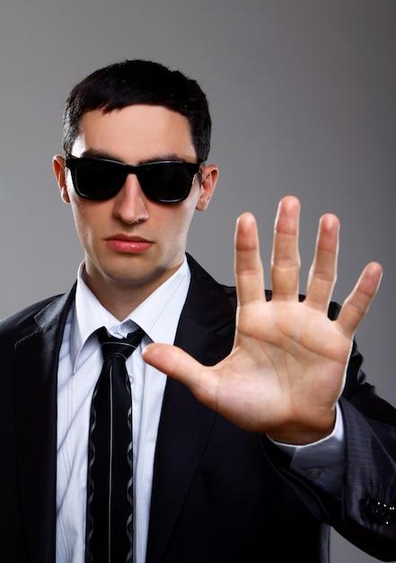 Ernstige man in pak toont stopteken Gratis Foto