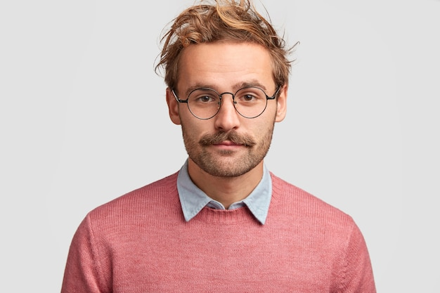 Ernstige man leraar met zelfverzekerde slimme look, heeft baard en snor, luistert naar het antwoord van de leerling, draagt roze trui, ronde bril Gratis Foto
