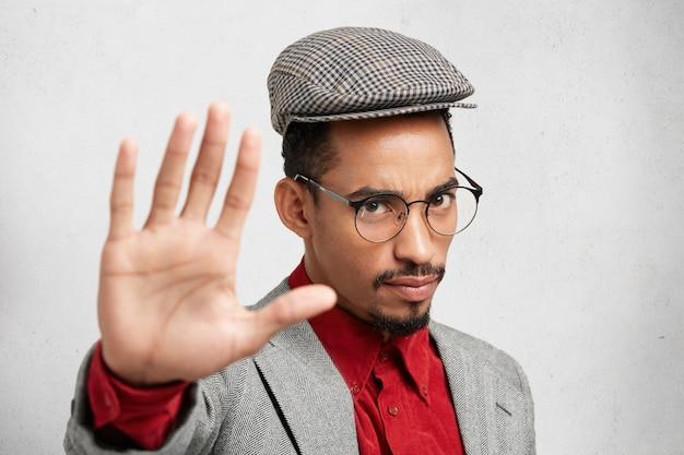 Ernstige man met donkere huidskleur maakt stopgebaar met de handpalm, zegt nee, drukt ontkenning of beperking uit. Gratis Foto