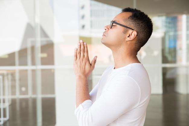 Ernstige man met gesloten ogen brengen handen in biddende positie Gratis Foto