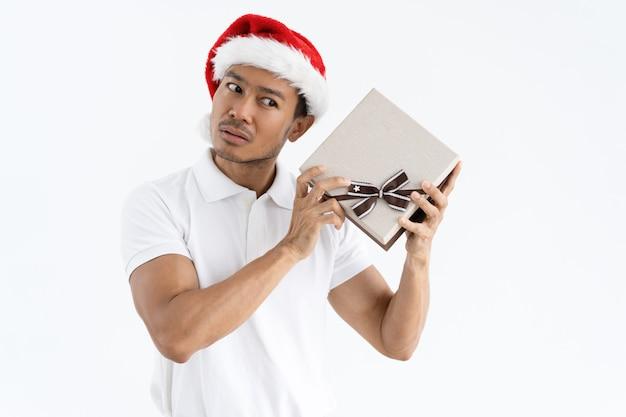 Ernstige man probeert te raden wat is in de doos van de gift van kerstmis Gratis Foto