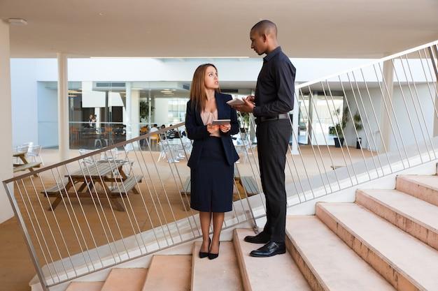 Ernstige mannelijke werkgever die vrouwelijke medewerker instrueert Gratis Foto