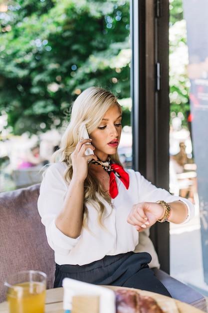 Ernstige mooie jonge vrouw die op de celtelefoon spreekt die haar polshorloge bekijkt Gratis Foto