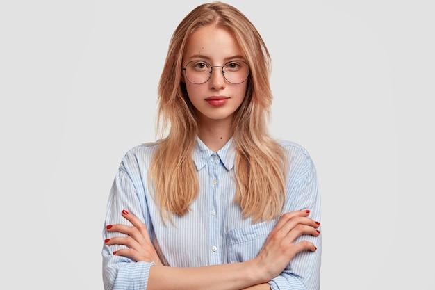 Ernstige mooie studente met bril, houdt de handen gevouwen, luistert aandachtig naar de lezing van de professor, draagt een elegant overhemd Gratis Foto
