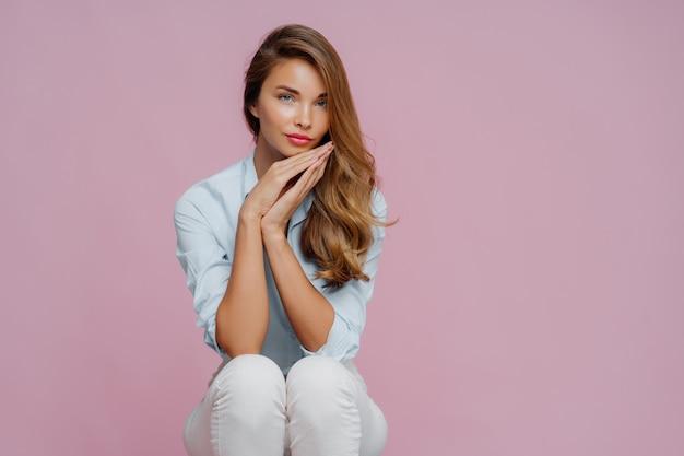 Ernstige mooie vrouw met lang haar, gekleed in shirt en broek Premium Foto