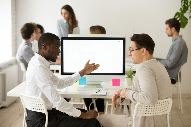 Ernstige multiraciale collega's die besprekings brainstormingsproject hebben samen in bureau Gratis Foto