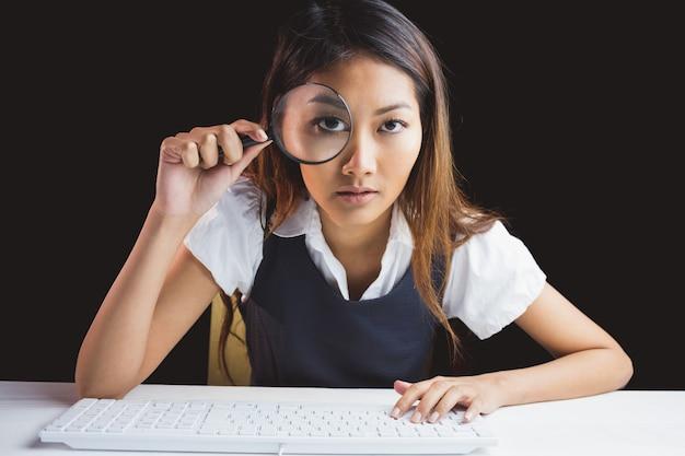 Ernstige onderneemster die door vergrootglas op zwarte achtergrond kijkt Premium Foto