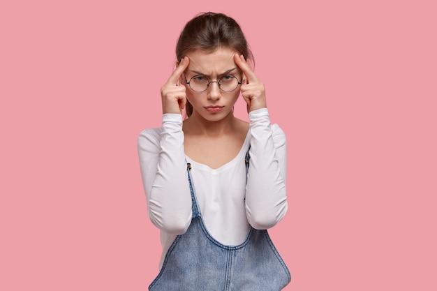 Ernstige ontevreden vrouw probeert zich te concentreren en zich te concentreren op het werk, houdt de handen vast aan de slapen, heeft vreselijke hoofdpijn, vermindert pijn door pijnstillers Gratis Foto