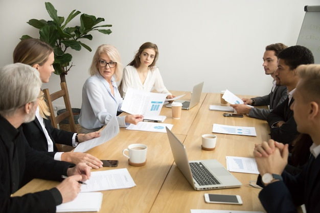 Ernstige oude onderneemster die collectief financieel rapport bespreken op teamvergadering Gratis Foto