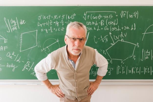 Ernstige oude professor in collegezaal camera kijken Gratis Foto