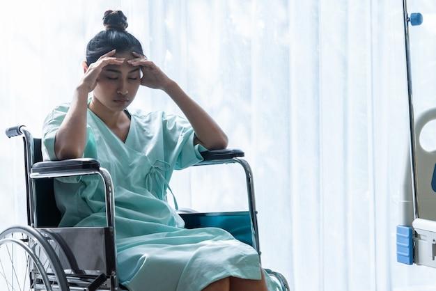 Ernstige patiënt zittend op rolstoel in het ziekenhuis. Premium Foto