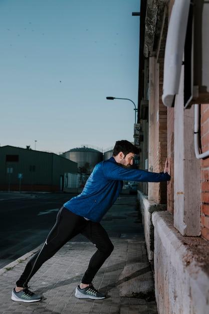 Ernstige sportman die op muur en het verwarmen leunt Gratis Foto