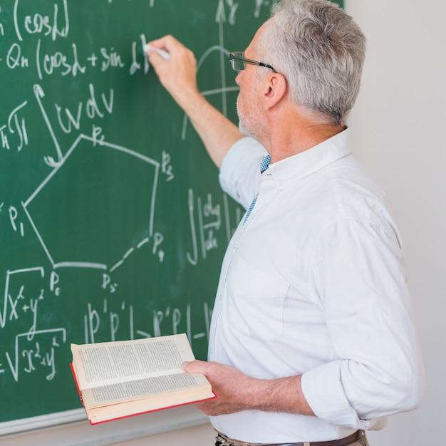 Ernstige spreker in glazen chalking formule op blackboard Gratis Foto