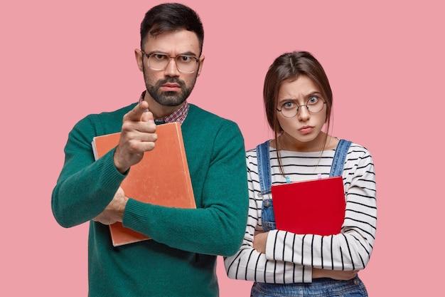 Ernstige strenge mannelijke professor houdt dik leerboek vast, wijst rechtstreeks naar je, mooie assistent met ronde bril staat dichtbij Gratis Foto