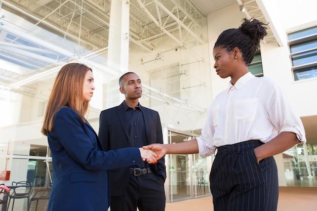 Ernstige strikte bedrijfsvrouwen die handen op kantoor schudden Gratis Foto