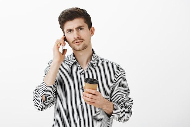 Ernstige strikte kaukasische bebaarde broer in gestreept overhemd, kopje koffie vast te houden en met gerichte uitdrukking aan de telefoon te praten, zich intens voelen bij het bespreken van belangrijke zakelijke bijeenkomst over grijze muur Gratis Foto