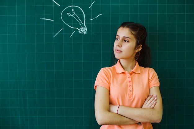 Ernstige student poseren voor het schoolbord Gratis Foto