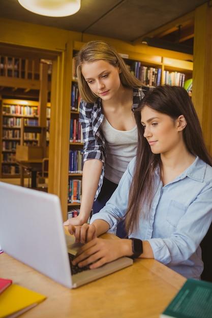 Ernstige studenten die laptop in bibliotheek met behulp van Premium Foto