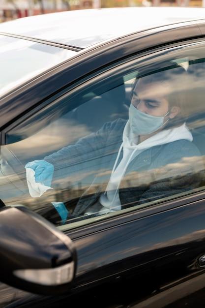 Ernstige taxichauffeur in doek masker zit in auto en stuurwiel met servet desinfecteren Premium Foto