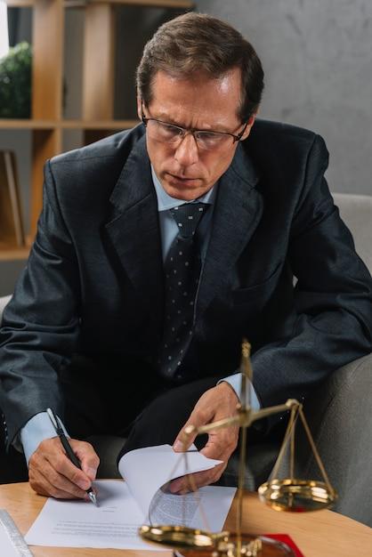 Ernstige volwassen mannelijke advocaat ondertekening contract met pen in de rechtszaal Gratis Foto
