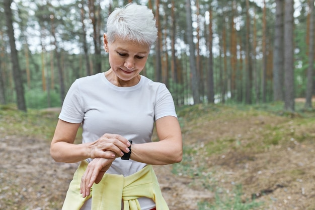 Ernstige volwassen vrouw atleet fitness tracker opzetten om de hartslag te controleren tijdens het hardlopen in het park Gratis Foto