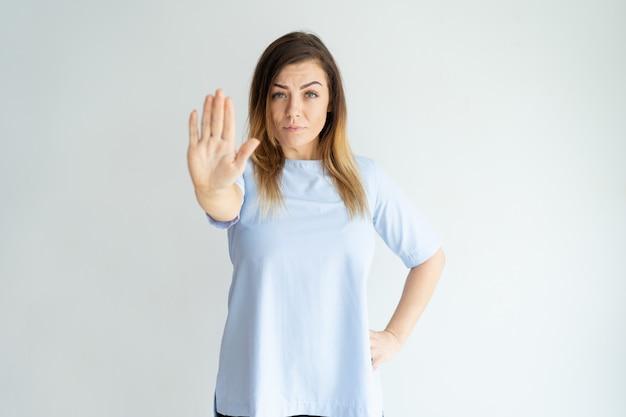 Ernstige vrouw die open palm of eindegebaar toont en camera bekijkt. Gratis Foto