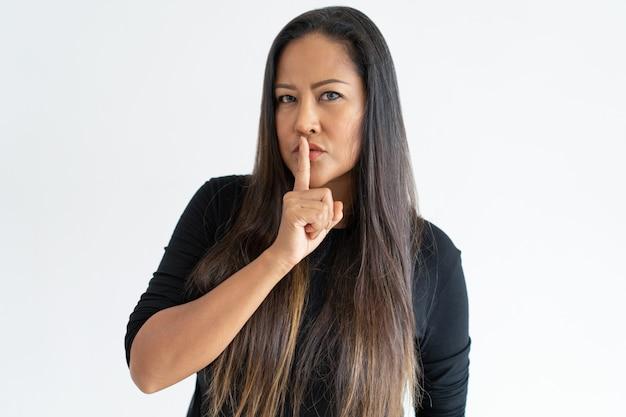 Ernstige vrouw van middelbare leeftijd stilte gebaar maken Gratis Foto