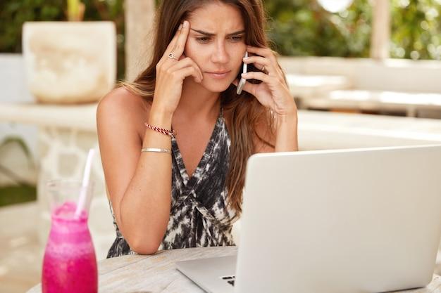 Ernstige vrouwelijke freelancer probeert een probleem op te lossen, praat met baas via mobiele telefoon, gericht op scherm van laptopcomputer, omringd met verse cocktail, werkt op afstand tijdens rust in resort Gratis Foto