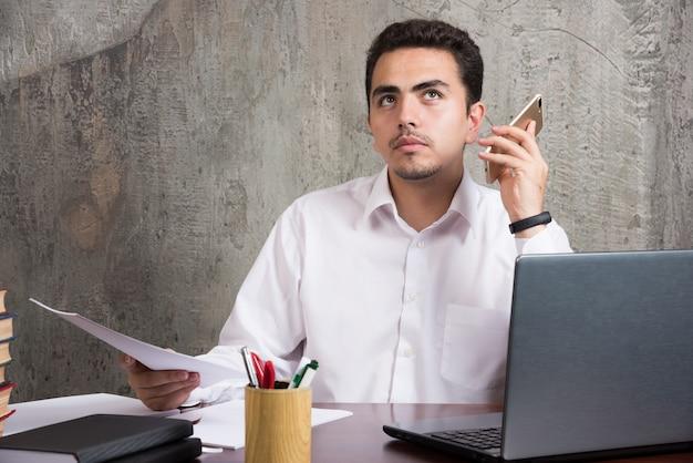Ernstige werknemer die voicemail van telefoon luistert en aan het bureau zit. hoge kwaliteit foto Gratis Foto