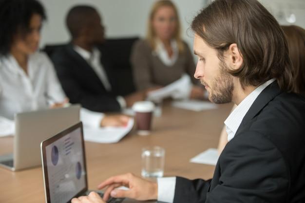 Ernstige zakenman die online aan laptop bij diverse groepsvergadering werken Gratis Foto