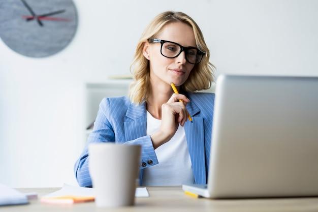 Ernstige zakenvrouw met behulp van laptop in heldere, moderne kantoren Premium Foto