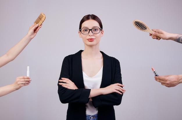 Ernstige zakenvrouw staat op een grijze rug in een zwarte jas, wit t-shirt en computer bril. haar armen gekruist. de verkeerde handen geven haar twee kammen en 2 lippenstiften. Premium Foto