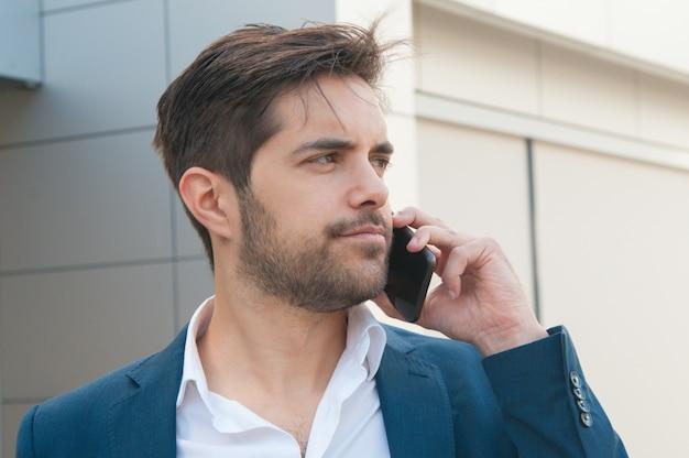 Ernstige zekere zakenman die op mobiele telefoon spreekt Gratis Foto
