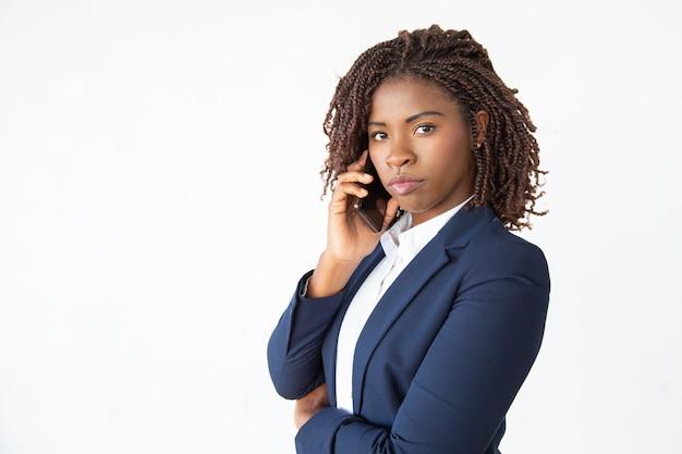 Ernstige zelfverzekerde bedrijfsleider die op mobiel spreekt Gratis Foto