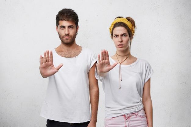 Ernstige zelfverzekerde jonge man en vrouw die allebei een stopgebaar maken met uitgestrekte armen, hun onenigheid of protest tonen Gratis Foto