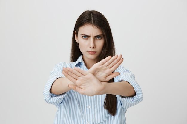 Ernstige zelfverzekerde vrouw stopbord, dwarse gebaar weergeven Gratis Foto